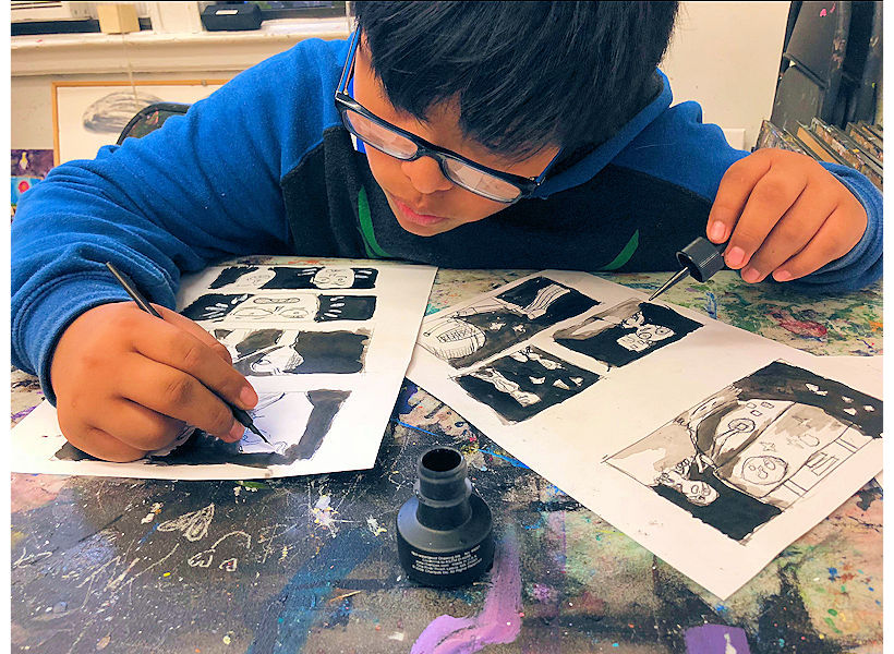 boy making ink story board in kids comics cartoon art class with instructor Jessica Hughes at the art studio ny uws kids art nyc