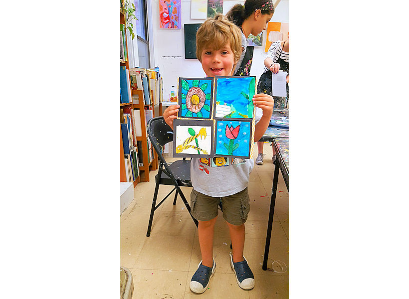 adorable 5-year-old boy happily sharing his still life mixed media drawing and painting artwork he made in his kindergarten kids art class at the art studio ny uws nyc instructed by an expert art educator in Wednesday after school art class