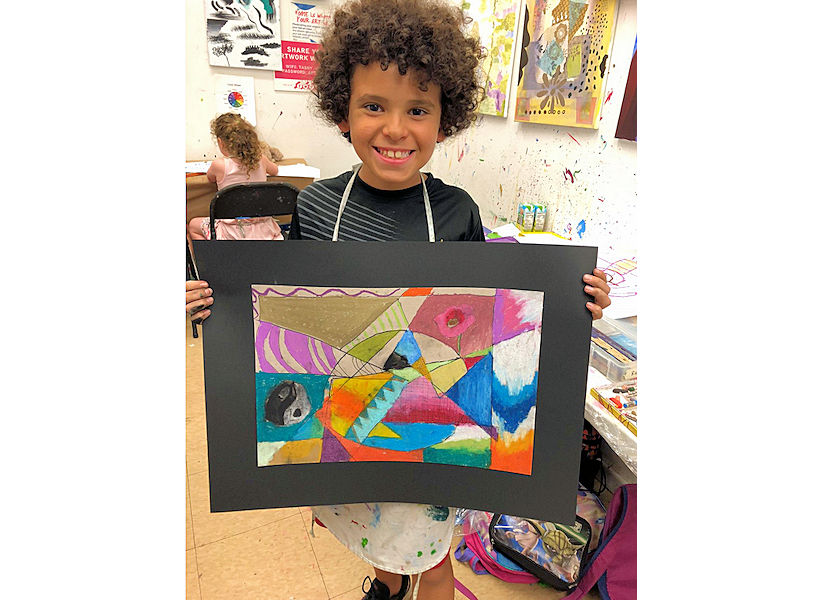 excited boy showing his cubist inspired abstract pastel painting from kids art classes ages 7 to 11 at the art studio ny uws fun for kids