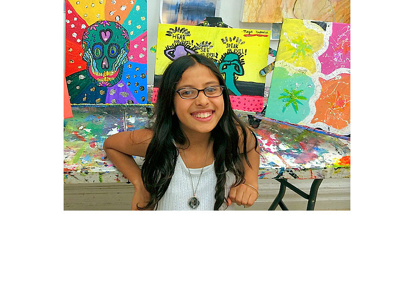 happy 8-year-old artist from kids art class after school in nyc with paintings on canvas at the art studio ny with engaging art instruction