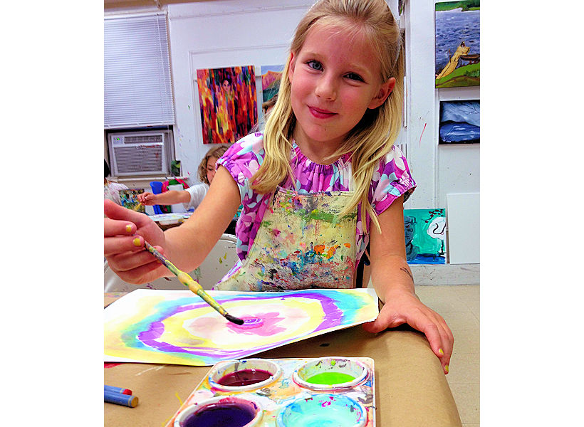 happy child making beautiful watercolor painting in kids art class at nyc top art studio