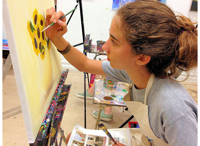 teen art student painting sunflower acrylic painting on canvas in teen painting class at nyc best art school uws